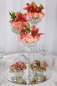 Beautiful 3 size vases with seasonal flowers and 2 mini fishbowls with flowers on a mirror base with tea light candles