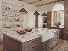 Marble counters, lime washed wood cabinets. Arched cut out to adjacent room. Lovely kitchen by Beth Webb Interiors