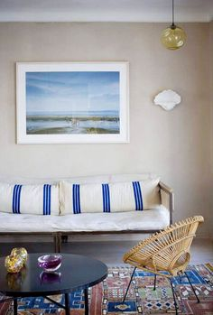 Bright and coastal themed living space with striped pillows and beach scenery on the wall