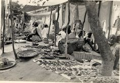 """Nigeria [?], view of """"Hausa market"""". Row of rugs [?] with goods laid out on them, baskets of goods on ground. Male and female adults and children sitting and standing beside rugs. Shelters made of cloths attached to vertical branches, over stalls. Wearing robes and head-gear. Medium: Gelatin silver print."""
