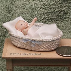 Dollhouse baby in a simple miniature oval basket woven from wire and crochet thread.