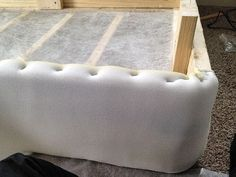 Wrap the box spring in foam padding and staple before covering in fabric. Looks so cushy and professional this way.