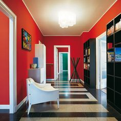 1920s Milan apartment... The apartment's most dramatic space mixes scarlet walls with a geometric floor and a couple of statement pieces. The ceiling extends on to the walls by half an inch, framing the space.