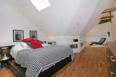 Interior:Double Size Bed With A Motif Blanket Also Red And Gray Pillows Complete A Standing Lamp And Two Picture On The White Wall Penthouse...