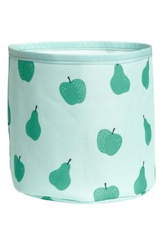 Light green/fruit. Small cylindrical storage basket in thick polyester with a printed pattern. Plastic coating inside. Height 6 in., diameter 6 in.