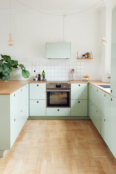 Basis 01 Küche in der Frontfarbe S2005-G20Y (grün) mit Griffen aus Eichenfurnier und einer Arbeitsplatte aus Eiche massiv.