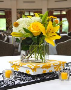 An all yellow, black, and white wedding reception, at the Audubon Tea Room, in New Orleans. Florals include, yellow asiatic lilies, yellow roses, white hydrangea, yellow button poms, and craspedia (a.k.a Billy Balls), arranged in a clear glass cube. A bright bouquet placed on a low, yellow and white pedestal, with a black and white table runner, surrounded by yellow votive candles.