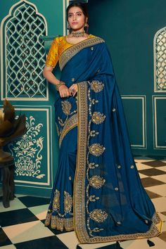 Regal Blue silk saree with mustard silk blouse. Embellished with resham work, sequins and zari work. Saree with Round Neck, Half Sleeve. It comes with unstitch blouse, it can be stitched to 32 to 58 sizes. #Silksaree #Indianwear #USA #Andaazfashion