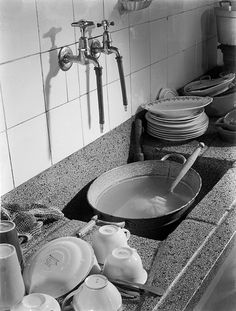 """""""De afwas met de hand.""""  My Oma had such a sink and high faucets with little rubber hoses to direct the flow.  But, my Oma had only cold water.  The hot water was what she heated on the two burner gas cooker."""