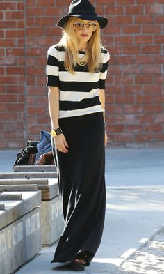 Rachel Zoe in black-and-white striped top, black maxi skirt, black hat, and gold jewelry.