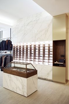 Eyewear store design by Lunetterie Générale. Shop in shop retail concept with brass panels, calacatta marble effect Neolith and display unit with British Museum inspired glass dome.