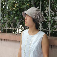 前にも後ろにもブリムがあるので、日除けに適しています。アジサイのようなアレンジで、梅雨のじめじめを楽しくしてくれる帽子です。