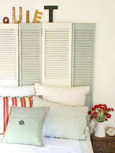 Love how  these old wood shutters are used as a headboard.