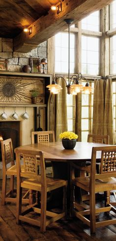 In the breakfast area of a Colorado home, William Sofield decorated the fireplace with a sunburst pattern composed of hundreds of nailheads, and grouped Robert Thompson chairs from the 1940s around an English oak table. Reclaimed wood is used throughout the house, as in the wormy chestnut flooring.