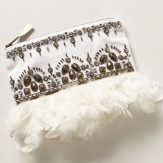 "❤️Anthropologie Clutch❤️ Used only a few times, small permanent marker mark inside, does not affect the bag at all. There may be a few loose/missing beads but nothing too noticeable. Also comes with a bag of replacement beads. I am not accepting offers on this, NO trades!  We love this lightweight clutch's dusting of soft white plumage and deco-beading.  Zip closure Cotton, polyester, plastic, rhinestones; polyester lining 6""H, 9""L, 0.25""D Anthropologie Bags Clutches & Wristlets"