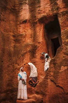"""Women entering a rock church through a narrow passage, Ethiopia"" // Photography: Mitchell Kanashkevich"