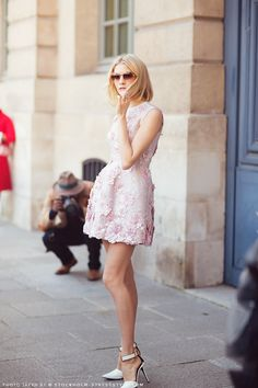 Elena Perminova in a pink flower petal applique dress, sunglasses, and ankle strap heels.