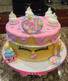 Shopkins Birthday Wish cake! Marble chocolate and vanilla cake with pink buttercream between four layers of cake and frosted with golden yellow buttercream, topped with pink fondant.