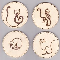 Set of four wooden coasters with stylised cats pyrography design. Created by Georgina Barnes.