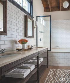 "Daltile supplied the wall and floor tile for the space known as the ""Treehouse Bathroom."" The vanity and medicine cabinets are from RH, and the sink and shower fittings are by Waterworks. A sconce by Circa Lighting and a Schoolhouse Electric fixture over the Kohler tub complete the look"