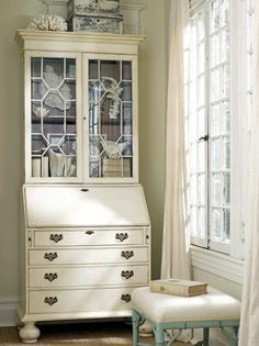 This beautiful neutral armoire is the perfect vintage piece to display corals and coastal accessories. The two glass doors sit above a secretary desk and set of drawers. French windows with floor-length curtains illuminate a blue-legged ottoman with a white upholstered cushion.