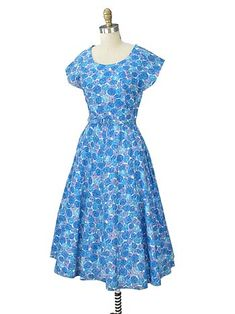 Pretty 1950s blue floral print day dress with flared tea length skirt. This is a one of a kind, true vintage dress with a fabulously feminine look. Perfect for a garden party or with the right accessories can easily transition to evening for informal dinners and cocktail parties.