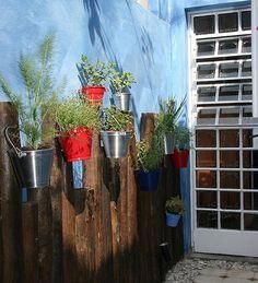 No corredor, as toras de eucalipto fixadas na parede sustentam minivasos de alumínio com ervas e temperos. Leves, esses vasos são ideais para serem pendurados. Na composição, aparecem no tom original ou pintados de vermelho e azul