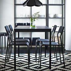 Una mesa de comedor negra con sillas del mismo color y una combinación de almacenaje en negro-marrón