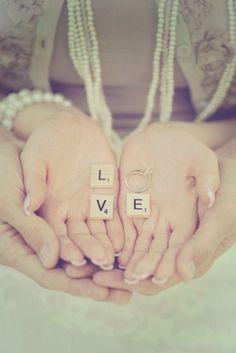 Manos con letras y un anillo de compromiso