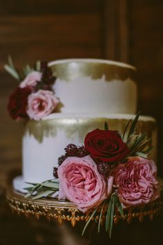 Two tiered, gold painted wedding cake with olive leaves, Pink O'Hara garden roses, astrantia and burgundy roses.   Flowers by Janie- Calgary Wedding Florist www.flowersbyjanie.com Cake: @whipptdessertsc  Photo: http://cednaphotography.com