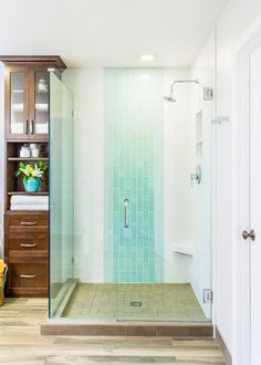 Two different accent tiles make a statement and add a pop of color against the large white tiles in this custom shower. A frameless glass enclosure creates a custom feel and lends contemporary flair to the transitional bathroom.