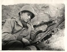 1943- U.S. soldier looks at a shattered rifle which was shot from the hands of his pal after Attu landing. His comrade died from his wounds.