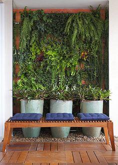 A treliça, da Marcenaria Bretas, com vários vasos de tempero.   Seixos de rio revestem as laterais da varanda,  escondendo os ralos