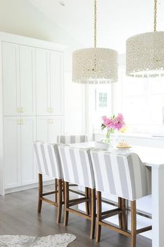Exquisite kitchen features a pair of Oly Studio Meri Drum Chandeliers illuminating a kitchen island lined with white and gray striped counter stools. Kitchen with white pantry cabinets paired with gold hardware alongside a metallic cowhide rug.