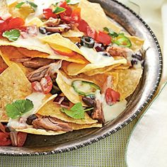 Serve a popular snack, Pulled Pork Nachos, for a carefree weeknight dinner. Pulled Pork Nachos are packed with protein and easy to assemble—ready in just 15 minutes. The pulled pork also makes delicious quesadillas, tacos, or sandwiches. Pulled Pork Nachos, Pulled Pork Recipes, Meat Recipes, Mexican Food Recipes, Appetizer Recipes, Appetizers, Crockpot Recipes, Cooker Recipes, Delicious Recipes