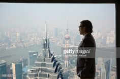 Stock Photo : Businessman looking out of window at Shanghai Bund