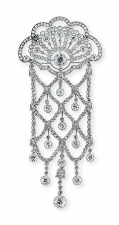 AN EARLY 20TH CENTURY DIAMOND BROOCH. The openwork fan-like surmount with old-cut diamond collet highlights within a millegrain-set rose-cut diamond frame, suspending an articulated similarly-set trellis like panel with diamond single-stone drop terminations, circa 1915, 9.8cm long