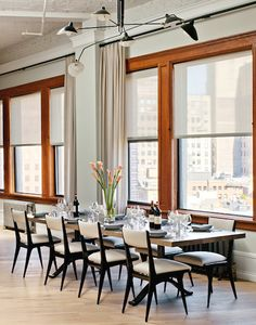 In this airy Lower Manhattan loft by Damon Liss, a Serge Mouille chandelier hangs over a BDDW Slab dining table with a oxidized maple top and blackened bronze wishbone base. Carlo di Carli dining chairs, 1954, from Donzella, complete the space.