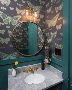 Lit by a clear glass and brass 2 light sconce, a round gold mirror is mounted to a wall clad in Cole & Son Butterflies Dragonflies Wallpaper above a gray stone sink vanity top fitted with a round sink with an antique brass faucet fixed in front of a peacock blue shiplap trim.