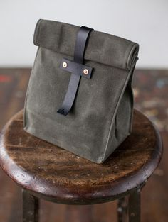 Olive Lunch Tote by Artifact Bag Co. - Be the talk of the office when you bring your lunch in this sturdy, waxed canvas lunch tote.   Handmade in my Omaha, Nebraska workshop using American materials. Color between canvas rolls and leather hides may vary slightly from what is depicted in the images.  American-made Horween leather strap, tab, and rivet washers   American-made 14 oz waxed canvas  Hand hammered solid copper rivets   Double stitched seams using heavy (size 138) American-made…