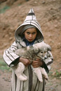 Moroccan boy holding a little dog.