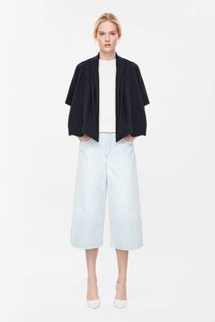 Made from modern technical fabric, this blazer is a flared A-line shape with draped lapels along the front. A loose, oversized fit, it has neat half sleeves, dropped shoulder seams and panelled detailing across the shoulders.