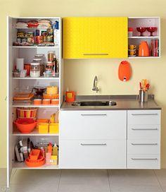 Utensílios e mantimentos compartilham o mesmo armário? A primeira providência é acomodá-los em prateleiras separadas. A prateleira mais baixa destina-se aos acessórios pouco usados. Se você faz grandes investidas culinárias diariamente, por exemplo, vale a pena usar o espaço para enfileirar assadeiras e fôrmas. A área ainda pode abrigar panela de pressão e produtos de limpeza para reposição – devidamente acomodados em um cestinho.