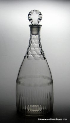 Georgian glass decanter Date : c1775 Period : George III Origin : Unknown, see additional information Colour : Clear Stopper : Ground, Scalloped disc Neck : Scale facet cutting Body : Tapered body form, engraved egg and dart band above a flute cut base Base : Polished Glass Type : Lead Size : 11 inches tall and 4 inches in diameter (including stopper)