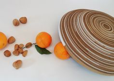 """Handmade bowl made by corrugated cardboard, totally protected with waterproofing paint.  The paper backs to be wood: concentric circles of cardboard, basic module for this line, evoke the sections of the trunks on which recount the years of the trees and rethink the value of paper. Long strips roll up on themselves until to become mass and volume, and then """"bowl""""."""