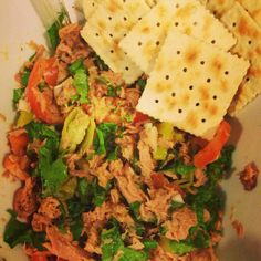Fresh tuna salad with lettuce, onions, tomatoes, yellow chili peppers in lemon with saltines