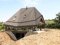Concrete base, one steel frame on top combined with façade woodframe carries A closed polygone wooden box. Vlieland