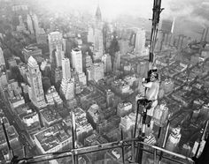 A bridgeman with U. Steel climbs atop the Empire State Building on Oct. He's one of 22 structual iron workers who erected a permanent five-station television tower on top of the Empire State Building. Photo, city view, history, black and white Empire State Building, Chrysler Building, Television Antenna, New York Architecture, Manhattan New York, Vintage New York, Construction Worker, Top Of The World, Historical Photos