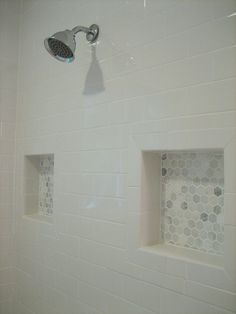 shower enclosure with white subway tiled walls and recessed tiled shower cubbies with Grecian White Marble Hex tile.