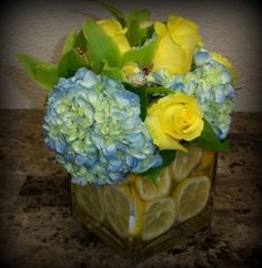 The sweet aroma of fresh lemons lining the vase make for a multi-sensory display with Blue/White Hydrangea, Green Cymbidium Orchids and Yellow Roses.
